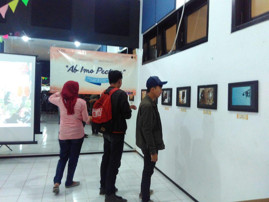 MENYIMAK - salah satu pengunjung Ab Imo perto terlihat fokus  memperhatikan pameran foto di acara tersebut.